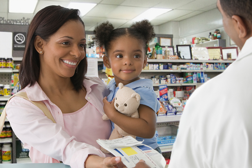 Mom holding daughter standing at pharmacy counter